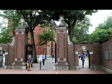 In this 2019 photo, pedestrians walk through the gates of Harvard Yard at Harvard University in Cambridge, Mass.