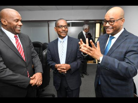 Craig Beresford (right), director of information and complaints at the Integrity Commission, speaks with Greg Christie (left), executive director, and retired Justice Seymour Panton, chairman, at the swearing-in of Beresford at the corruption watchdog's