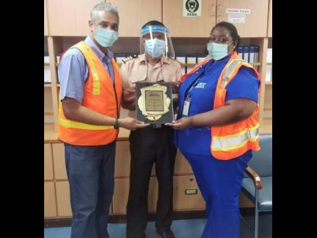 Captain Ovitigala Nalin Nirosha (centre) of the 'CSCL LONG BEACH' is presented with a plaque commemorating the ship's first call to the port of Kingston by Jamaica Freight & Shipping's Operations Manager,  Christopher Magnus,  and Jamaica Freight &