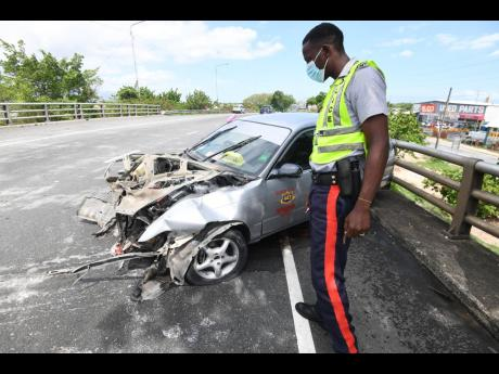 Constable C. Brown examines a Toyota Corolla Wagon motor car that ran into the rail of the flyover bridge at Six Miles, spinning out of control and stopping on the opposite side. The driver of the vehicle, who was rushed to hospital with injuries, was dri