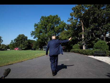 US President Donald Trump waves as he departs after speaking with reporters on the lawns of the White House on Wednesday, July 29. The United States economy shrank by a historic record 32.9% in the June quarter.