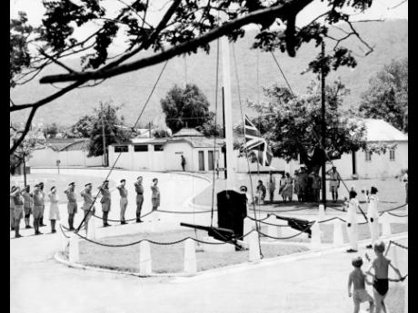 The commander of the Caribbean area, Brigadier Derek Lister, and members of the Staff and Services of the Headquarters Caribbean Area saluting the Union Jack as it was slowly lowered for the last time, while two buglers of the Jamaica Regiment sounded the