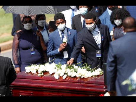 Mourners place flowers on the casket of Rep John Lewis at South-View Cemetery, yesterday, in Atlanta. Lewis, who carried the struggle against racial discrimination from Southern battlegrounds of the 1960s to the halls of Congress, died on July 17.