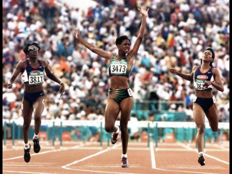 Deon Hemmings-McCatty (centre) celebrates after winning the 400m hurdles at the Atlanta Olympics in 1996.