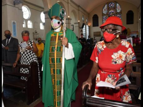Bishop of Kingston Dr Robert Thompson enters Kingston Parish Church wearing his ceremonial garb for the last time during the Emancipation service, for which he was the officiating minister, on Sunday.