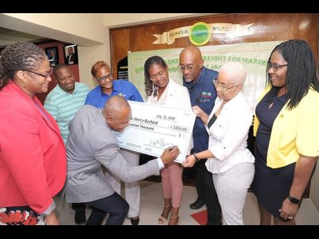 Members of the Customs Brokers and Freight Forwarders Association of Jamaica (CBFFAJ) came out in support of their colleague custom broker, Patrice Henry-Burford (second right), who requires urgent medical care abroad. Here Henry-Burfurd accepts the donati