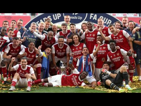 Arsenal's Pierre-Emerick Aubameyang holds the trophy as players celebrate after the FA Cup final match between Arsenal and Chelsea at Wembley stadium in London, England, Saturday, August 1, 2020.