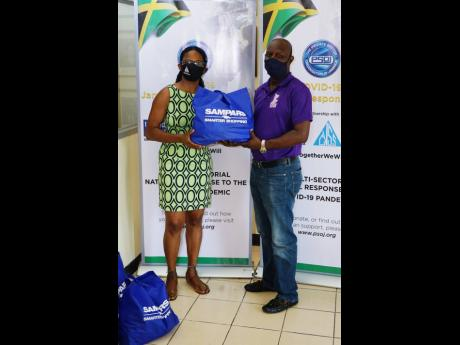 Shelly-Ann Lawson Francis (left), executive director of the Council of Voluntary Social Services, presents one of the food and care packages to O'Neil Cruikshank, cricket operations and development manager at the Jamaica Cricket Association (JCA). The JC