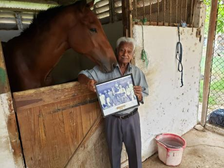 Former jockey and trainer Harry Jaghai shows off a picture of one of his three wins as a jockey at the stable area at Caymanas Park, recently.