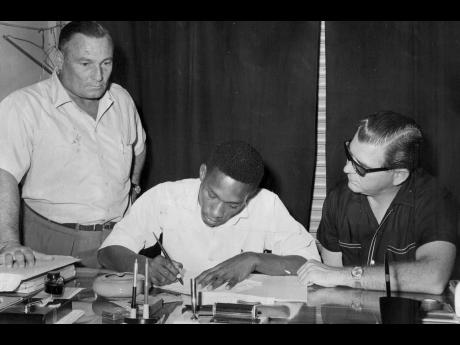 Jamaica footballer, Asher Welch (centre), signs a contract to play professional football with the Baltimore Football Club while club representative Deryck Tomlinson (right) and Jorge Penna, Jamaica national football coach look on.