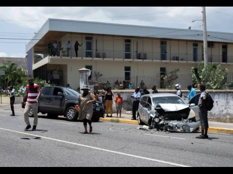 Onlookers gather at the scene of a motor vehicle accident on Half-Way Tree Road, St Andrew, in the vicinity of FedEx involving a Nissan Note, a Volkswagen Amorak and a Honda CRV on Wednesday, July 29, 2020. The driver of the Nissan Note was rushed to the h