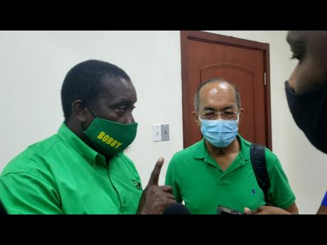 Party Chairman Robert Montague fields questions from journalists in Montego Bay on Sunday. To his left is JLP General Secretary Dr Horace Chang.