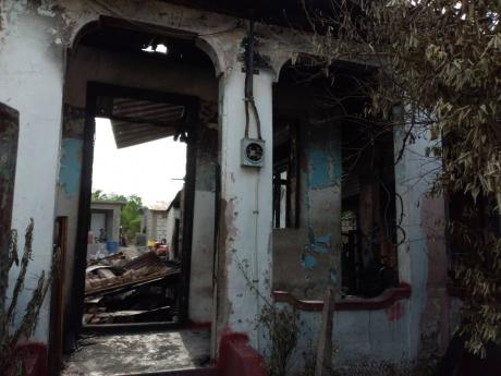 The firebombed house at 11 Margaret Street in east Kingston where a 64-year-old man was killed earlier.
