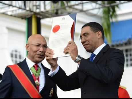 Governor General Sir Patrick Allen looks on while  Prime Minister  Andrew Holness shows the instrument of appointment.