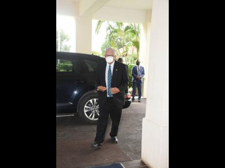 Karl Samuda makes his way into King's House to witness the swearing-in of Andrew Holness as prime minister for the third time.