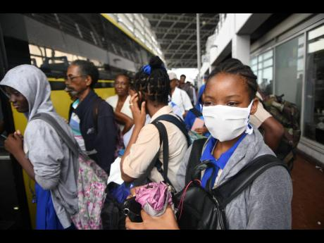 A high-school student wears a cloth face mask at the Half-Way Tree Transport Centre on Wednesday, March 11, a day after the first coronavirus case was recorded in Jamaica. Some administrators have ordered that students only wear branded masks to school.