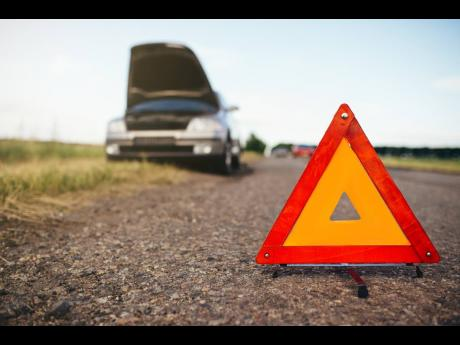 Broken car concept, breakdown triangle on asphalt road. Problem with vehicle, warning sign