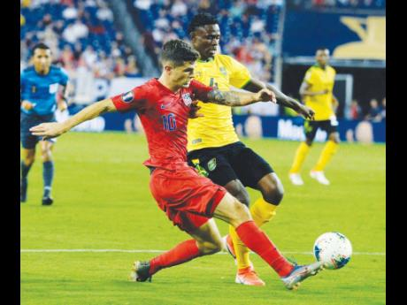United States midfielder Christian Pulisic (left) gets past Jamaica midfielder Andre Lewis to provide a cross during the second half of a Concacaf Gold Cup semi-final match in Nashville, Tennessee, on Wednesday, July 3, 2019.