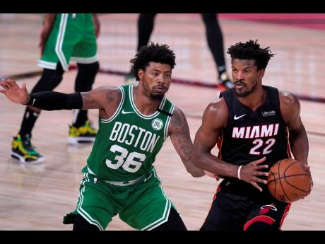 Boston Celtics' Marcus Smart (left) defends as Miami Heat's Jimmy Butler looks to make a pass during the second half of an NBA conference final basketball game, Saturday, September 19, 2020, in Lake Buena Vista, Florida.