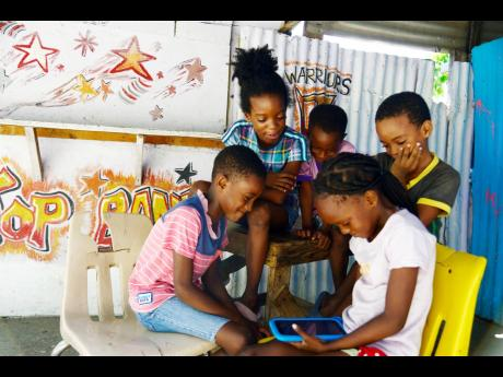 Children in Bowerbank, Kingston, are glued to a video being played on a tablet on Tuesday. Backtracking on a plan to phase in face-to-face classes on October 5, the Government announced on Tuesday that students will be reliant on a mixture of online and TV