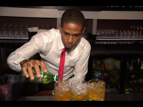 Milton Wisdom pours ginger ale to rock glasses.