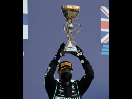 Bottas of  Finland celebrates  on the podium  after winning the Russian Formula One Grand Prix.