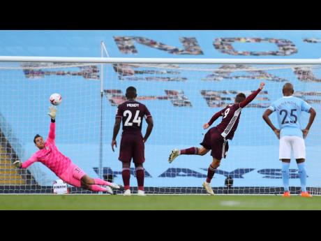 Leicester's Jamie Vardy (second right) scores his side's first goal of the game from the penalty spot during their English Premier League match against Manchester City at the Etihad Stadium in Manchester, England, yesterday.