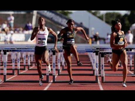 In this file photo from June 2019, University of Arkansas' Janeek Brown (left) edges out Louisiana State University's Tonea Marshall (centre) and Southern California's Chanel Brissett to win the women's 100 hurdles during the NCAA outdoor track and