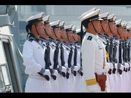 In this 2019, file photo, Chinese People's Liberation Navy sailors stand in formation on the deck of a type 054A guided missile frigate 'Wuhu' as it docks at Manila's South Harbour for a four-day port call in Manila, Philippines. US-China friction
