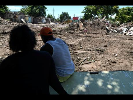 Residents of White Wing observe a cleared section of the southwest St Andrew community on Monday.