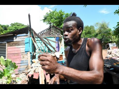 Dane Nicholson speaks to journalists as bulldozers began demolition of informal houses at White Wing, near Three Miles, on Monday. The National Housing Trust will be building a residential complex on the property.