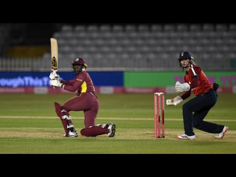Stafanie Taylor of the West Indies plays a shot while England wicketkeeper Amy Jones looks on during the first Vitality T20 between England Women and West Indies Women at the Incora County Ground on September 21, 2020 in Derby, England.