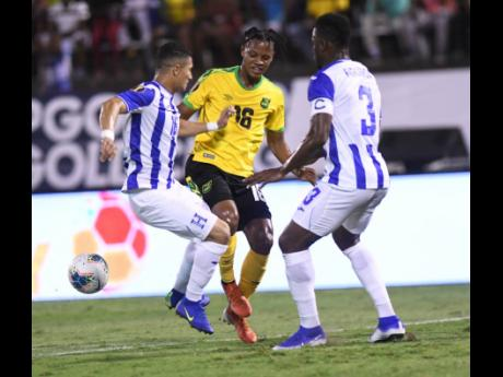 Jamaica's Peter Vassell (centre) attempts to get between Honduran players Hector Castellanos (left) and Maynor Figueroa, during their Concacaf Gold Cup match held at the National Stadium on June 18, 2019. Jamaica won 3-2.