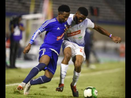 Mount Pleasant's Cardel Benbow (left) and Emelio Rousseau of Portmore United in a tussle for possession in the Red Stripe Premier League Semi-final at the The National Stadium on Monday April 15, 2019.