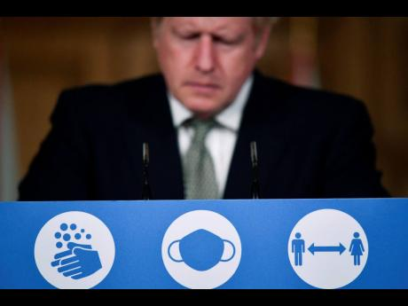 Britain's Prime Minister, Boris Johnson, listens during a coronavirus briefing in Downing Street, London, on Monday, October 12. AP