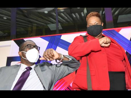 Rudoph Brown/Photographer  CEO of First Heritage Co-operative Credit Union Limited Roxann Linton greets Chairman Balvin Vanriel with an elbow bump at the annual general meeting on September 17 at the Jamaica Conference Centre in Kingston.