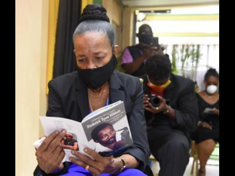 Doreen Hibbert, widow of the  late Toots Hibbert, was overcome with emotions as she looks through the funeral programme   during a private funeral service for the late reggae icon, at Perry's Funeral home yesterday.