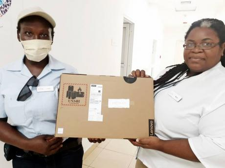 Fiona Morrison-Martin (left), collects a new Lenovo laptop from Foundation Coordinator Talcia Peart-Peters. Morrison-Martin's daughter, Kashera, won the laptop which was donated through the efforts of Diana Winters and the Canadian Travel agents. Morriso