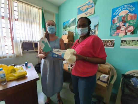 Carla Gullotta, executive director of Stand Up For Jamaica, hands over 17,000 face masks and nine thermal scanners to Winsome Harris, director of public procurement at the Department of Correctional Services.