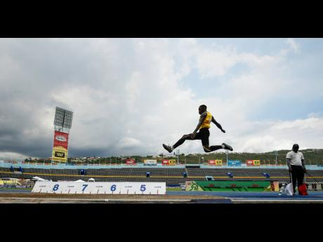 Excelsior High School's Derick Robinson mid-flight during the long jump section of the decathlon at the ISSA/GraceKennedy Boys and Girls' Athletics Championships at the National Stadium on Wednesday, March 27, 2019. Anthony Davis, who is running for th