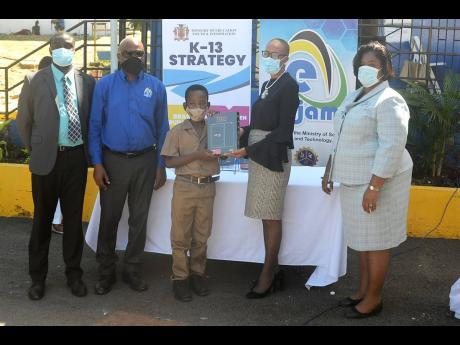 Education Minister Fayval Williams (second right) presents a tablet to Chance Robinson (centre), a grade five student of the Barrett Town Primary School in St James, during a ceremony where tablets were presented to Barrett Town Primary School and John's