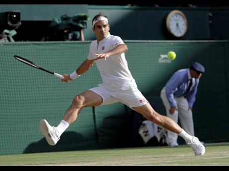 Switzerland's Roger Federer returns the ball to Spain's Rafael Nadal during a men's singles semifinal match on day eleven of the Wimbledon Tennis Championships in London, England on Friday, July 12, 2019.