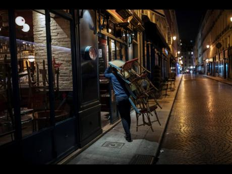 In this October 17, 2020 file photo, a waiter closes a bar terrace in Paris. Virus cases are surging across Europe and many US states, but responses by leaders are miles apart, with officials in Ireland, France and elsewhere imposing curfews and restrictin