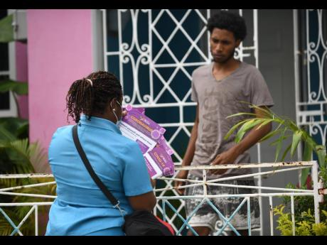A healthcare worker gives leaflets with COVID-19 information to a resident of Waterford in Portmore, St Catherine, earlier this month as part of intervention measures following a spike in cases there.
