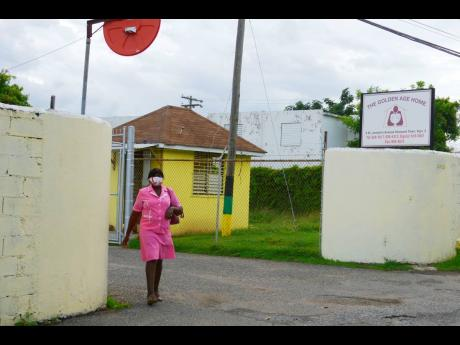 A woman exiting the Golden Age Home in Vineyard Town, Kingston, yesterday. A cluster of COVID-19 cases have been discovered at the elderly care facility.