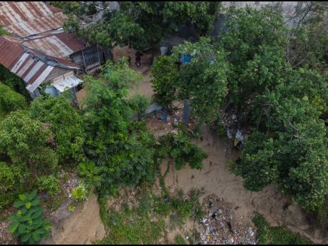An aerial photograph of a house on Barrett Street in Spanish Town, St Catherine, on Friday, July 17, 2020. The dwelling inches closer to the Rio Cobre with each heavy downpour of rainfall as a result of soil erosion.