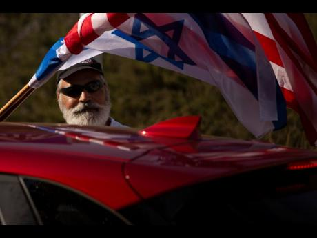 An Israeli supporter of the re-election of US President Donald Trump waves American and Israeli flags from a car at a rally outside of the US Embassy in Jerusalem on Tuesday.