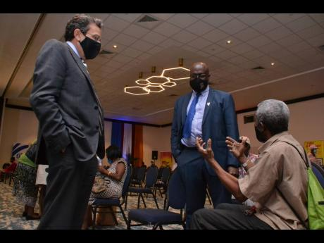 RJRGLEANER Communications Group Chairman Joseph M. Matalon (left) and Group CEO Gary Allen in discussion with shareholder Clevi Johnson, who is visually impaired, at yesterday's annual general meeting.