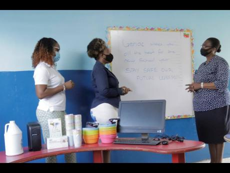 General Accident Insurance Company's Colesha Mahoney (left) and Kerry-Ann Spencer (centre) present Maisie Green Learning Centre Principal Charmaine Bennett with the computer and other items donated to the school recently.