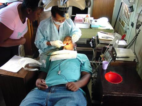 A patient receives treatment at the Portmore Dental Clinic recently.